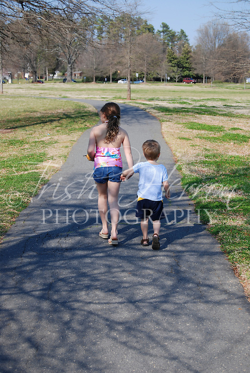 A young girl and her little brother hold hands as they walk in the park.