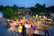 The Skeen family of Pearland, Texas, outside their home with all of their possessions. Published in Material World: A Global Family Portrait, pages 136-137. Ricky Skeen and his wife Pattie Skeen, with their two children, Michael and Julie. From Peter Menzel's Material World Project that showed 30 statistically average families in 30 countries with all of their possessions.