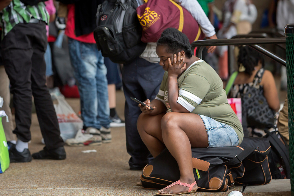 A resident of Savannah looks at her cell phone while waiting in line at the Savannah Civic Center before evacuating from he path of Hurricane Irma, Saturday, Sept., 9, 2017 in Savannah, Ga. (AP Photo/Stephen B. Morton)