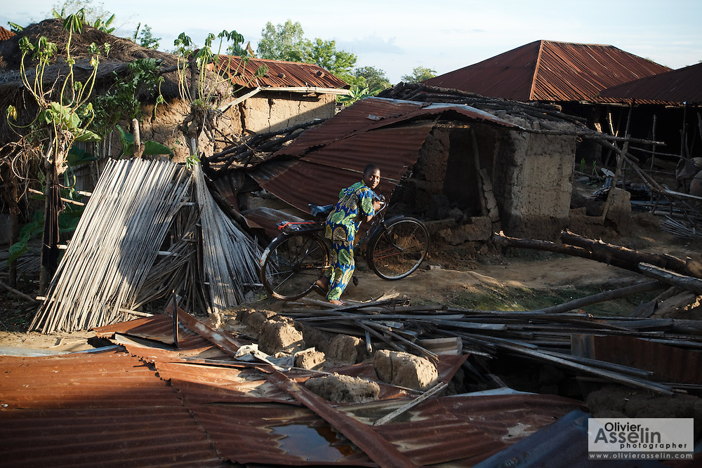 A boy pushes his bicycle through destroyed houses in the village of Kpoto, Benin on Tuesday October 26, 2010.  Waters have receded in Kpoto, but most of the village was literally flattened by floods that have hit Benin over the past few weeks..