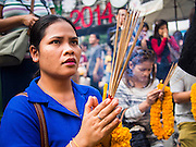 31 DECEMBER 2013 - BANGKOK, THAILAND:  A woman prays at Erawan Shrine on New Year's Eve in Bangkok. Hundreds of thousands of people pack into the Ratchaprasong Intersection in Bangkok for the city's annual New Year's Eve countdown. Many Thais go the Erawan Shrine and Wat Pathum Wanaram near the intersection to pray and make merit.    PHOTO BY JACK KURTZ