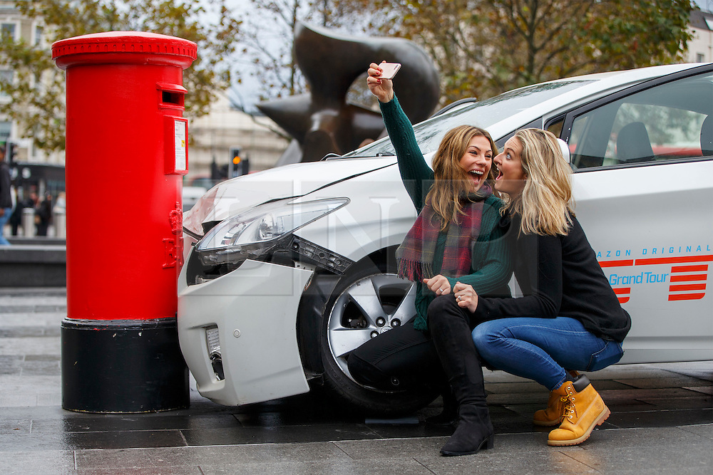 © Licensed to London News Pictures. 15/11/2016. London, UK. Two women take selfies with a car crash stunt to promote Amazon Prime's forthcoming series 'The Grand Tour' in King's Cross Square, London on 15 November 2016. Photo credit: Tolga Akmen/LNP
