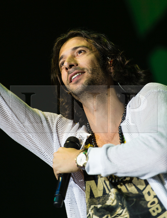 """© Licensed to London News Pictures. 26/05/2015. London, UK.   Magic performing live at Wembley Arena, supporting headliner Maroon 5.   In this picture - Nasri.  Magic! Is a Canadian reggae fusion band,  composed of songwriter and record producer Nasri (lead vocals, Guitar), Mark Pellizzer (guitar, vocals), Alex Tanas (drums) and Ben Spivak (bass, vocals).  They are most well-known for their debut single, """"Rude"""", which peaked at number-one in seven countries.  Photo credit : Richard Isaac/LNP"""