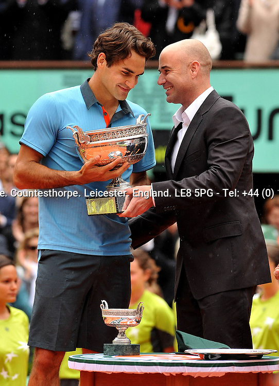 Roger FEDERER (SUI) the new French Open 2009 Men's Singles Champion being presented the winner's trophy by the last man to hold all 4 Grand Slam titles Andre Agassi<br /> <br /> Roger FEDERER (SUI) Robin SODERLING (SWE) 6-1 7-6 (7-1) 6-4<br /> <br /> Tennis - French Open - Day 15 - Sun 07 Jun 2009 - Roland Garros - Paris - France<br /> <br /> &copy; CameraSport - 43 Linden Ave. Countesthorpe. Leicester. England. LE8 5PG - Tel: +44 (0) 116 277 4147 - admin@camerasport.com - www.camerasport.com