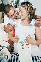 Expectant couple with baby clothes
