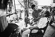 A man gets a shave at a street-side barber in Kolkata, India
