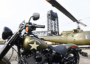 "A UH-1 ""Huey"" helicopter lands behind a Harley-Davidson Softail Slim S motorcycle to escort veterans to America's Parade in New York on Veterans Day, Wednesday, Nov. 11, 2015, in Kearny, NJ.  Harley-Davidson announced the extension of ""Operation Personal Freedom: Ride Free,"" free Riding Academy motorcycle training to all active-duty military and veterans. (Photo by Diane Bondareff/AP Images for Harley-Davidson)"