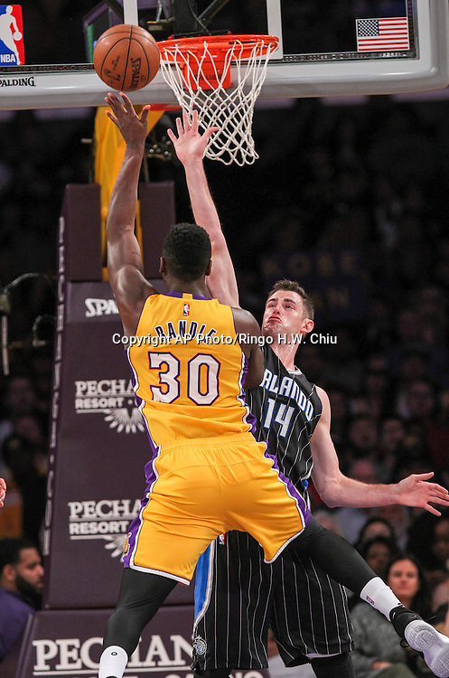 Los Angeles Lakers forward Julius Randle, left,  shoots against Orlando Magic center Jason Smith during the first half of an NBA basketball game Tuesday, March 8, 2016, in Los Angeles.  (AP Photo/Ringo H.W. Chiu)