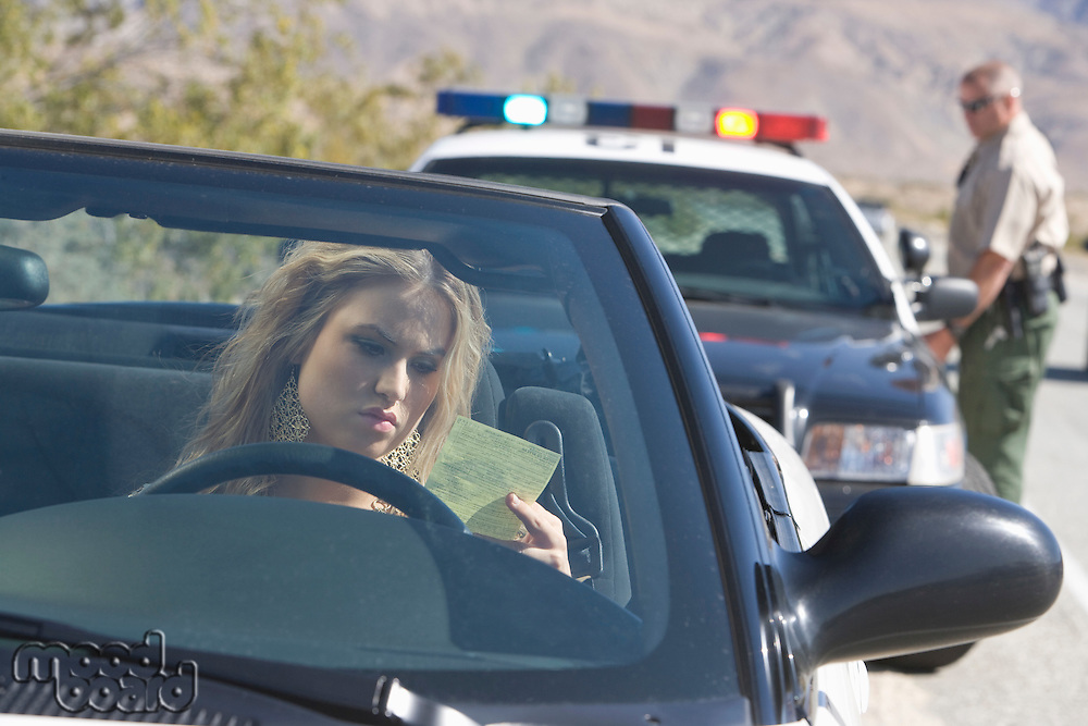 Young woman reading speeding ticket, policeman in background