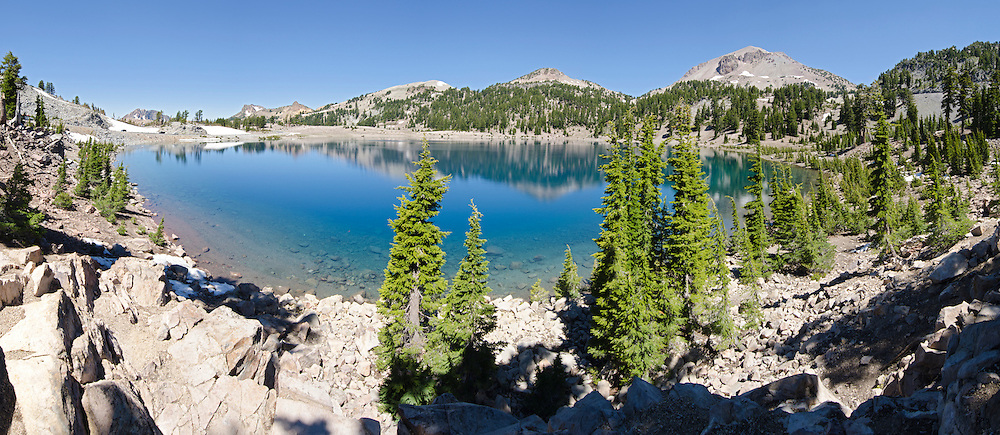 Panorama of the blue water of Lake Helen below Brokeoff Mountain, Mount Diller, Pilot Pinnacle, Ski Heil, Eagle and Lassen Peaks in Lassen Volcanic National Park, California.
