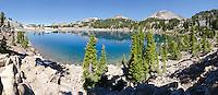 Panorama of the blue water of Lake Helen below Brokeoff Mountain, Mount Diller, Pilot Pinnacle, Ski Heil, Eagle and Lassen Peaks in Lassen Volcanic National Park, California.