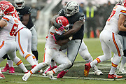 Kansas City Chiefs running back Spencer Ware (32) gets stuffed by Oakland Raiders defensive tackle Stacy McGee (92) on a first quarter run for no gain during the 2016 NFL week 6 regular season football game against the Oakland Raiders on Sunday, Oct. 16, 2016 in Oakland, Calif. The Chiefs won the game 26-10. (©Paul Anthony Spinelli)