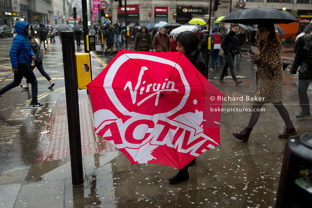 Storm Georgina swept across parts of Britain and in central London, lunchtime office workers were caught out by torrential rain and high winds, on 24th January 2018, in London, England. Pedestrians resorted to leaping across deep puddles at the junction of New Oxford Street and Kingsway at Holborn, the result of overflowing drains. Fourth in a sequence of eight photos.