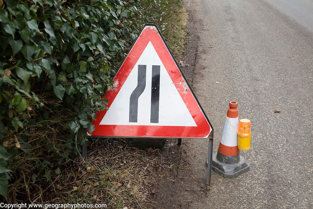 Red triangular sign for road narrowing on village street, UK