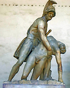 Statue of Menelaus supporting the body of Patroclus in the Loggia della Signoria, Florence, Italy. Now a statue of a man in armour supporting the dying nude body of his comrade, it originated as 2 headless torsos, but underwent extensive improvisatory restorations which altered the statue significantly. The nucleus of the sculpture was made in late 1st century AD as a Roman copy of a Hellenistic original. It underwent changes and adjustments regularly all the way until 1830.