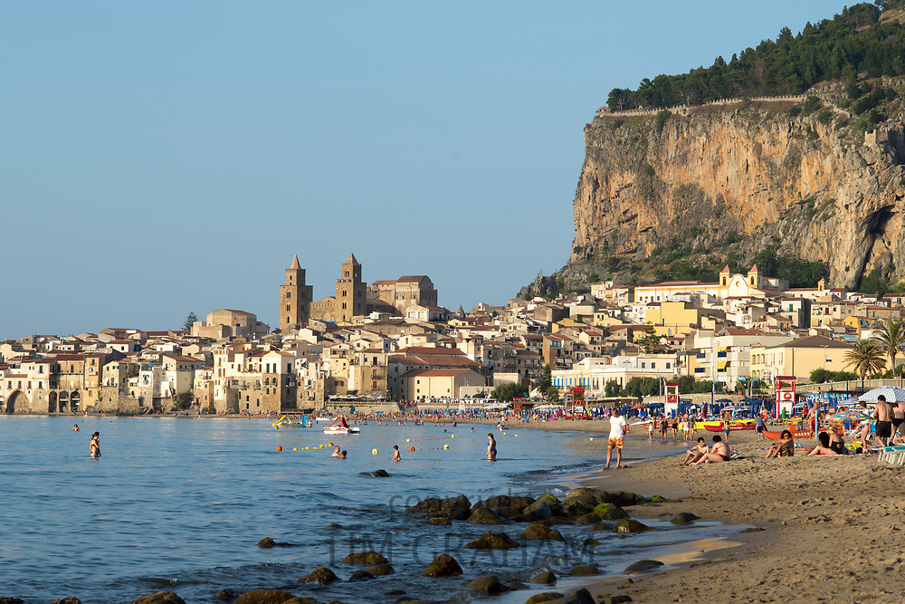 Tourists in coastal town of Cefalu with Baroque style architecture in Northern Sicily, Italy