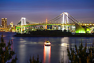 Illuminated Tokyo Rainbow Bridge at night with the Tokyo Toewer behind. The bridge connects Odaiba island to the  Minato district acros Tokyo Bay.