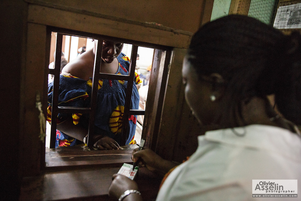 A staff member serves a customer at the Koumassi General Hospital in Abidjan, Cote d'Ivoire on Friday July 19, 2013.