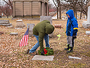 14 DECEMBER 2019 - DES MOINES, IOWA: NICHOLAS NEWELL and his son, ALEX NEWELL, 6, both from Des Moines, place a Christmas wreath on a veteran's gravestone. Volunteers working with Wreaths Across America placed Christmas wreaths on the headstones of more than 600 US military veterans in Woodland Cemetery in Des Moines. The cemetery, one of the first in Des Moines, has the graves of veterans going back to the War of 1812.      PHOTO BY JACK KURTZ