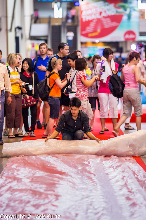 01 OCTOBER 2012 - BANGKOK, THAILAND:  A worker rolls out the red carpet during reopening ceremonies at Don Mueang International Airport in Bangkok Monday. Don Mueang International Airport is the smaller of two international airports serving Bangkok, Thailand. Suvarnabhumi Airport, opened in 2006 is the main one. Don Mueang was officially opened as a Royal Thai Air Force base on 27 March 1914 and commercial flights began in 1924. Don Mueang Airport closed in 2006 following the opening of Bangkok's new Suvarnabhumi Airport, and reopened as a domestic terminal for low cost airlines after renovation on 24 March 2007. Closed during the flooding in 2011, Don Mueang was again renovated and reopened in 2012 as the airport for low cost airlines serving both domestic and international passengers. On Monday, Air Asia, Asia's leading low cost airline, transferred all of their flight operations to Don Mueang and the airport was officially reopened. Suvarnabhumi International Airport is already over capacity and Don Mueang's importance as a hub is expected to grow.   PHOTO BY JACK KURTZ