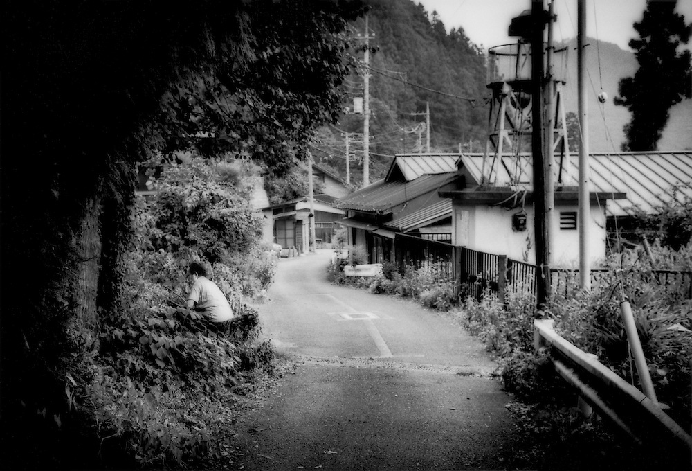 Rural young leaving the old behind & isolated for work in the city / A spry elderly woman in a village of elderly people, takes her machete to overgrown weeds.  Otaki, Saitama Prefecture, Japan.