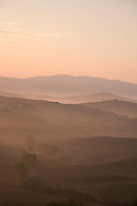 A dawn view over the misty hills of Val d'Orcia, Tuscany, Italy