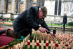 © Licensed to London News Pictures.06/11/2013. London, UK. A veteran soldier prepares the Field of remembrance at Westminster Abbey. Every November the annual Field of Remembrance at Westminster Abbey is organised and run by The Poppy Factory. This year officially it will be opened on Thursday 7 November. Remembrance crosses are provided so that ex-Service men and women, as well as members of the public, can plant a cross in memory of their fallen comrades and loved ones.Photo credit : Peter Kollanyi/LNP