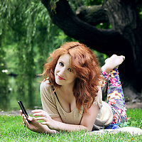 Smiling young woman playng with her mobile phone and relaxing at park