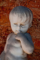 Close-up of an ancient marble statue of a cute toddler on Isola San Michel in Venice, Italy.