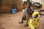 A girl rests her head on a boy's lap in Katiola, Cote d'Ivoire on Friday July 12, 2013.