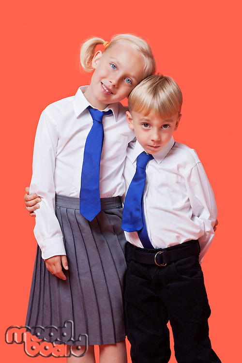 Portrait of young siblings in school uniform with arm around over orange background