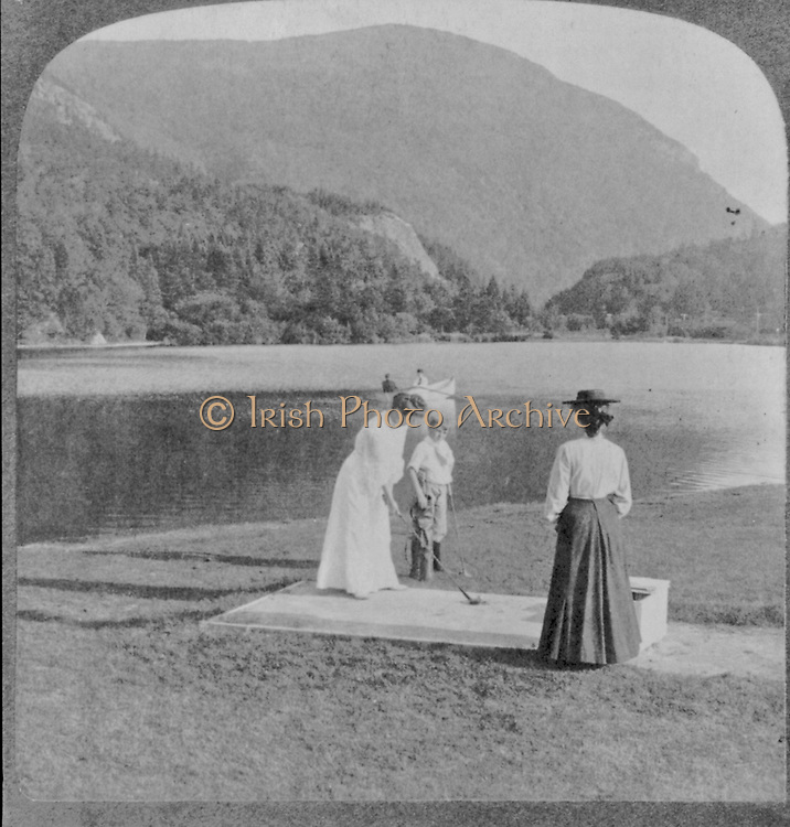 Summer sports in the heart of the White Mountains - Elephant's Head from above Crawford's, N.H. Woman and boy with golf clubs in foreground, 2 people in boat on lake, mountain in background. stereograph.  c1905