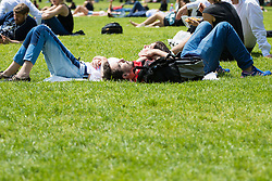 Green Park, London, June 6th 2016. A couple relax on the grass in Green Park as London basks in glorious summer sunshine with highs of 24º expected.