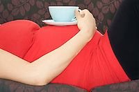Pregnant woman with drink on sofa mid section
