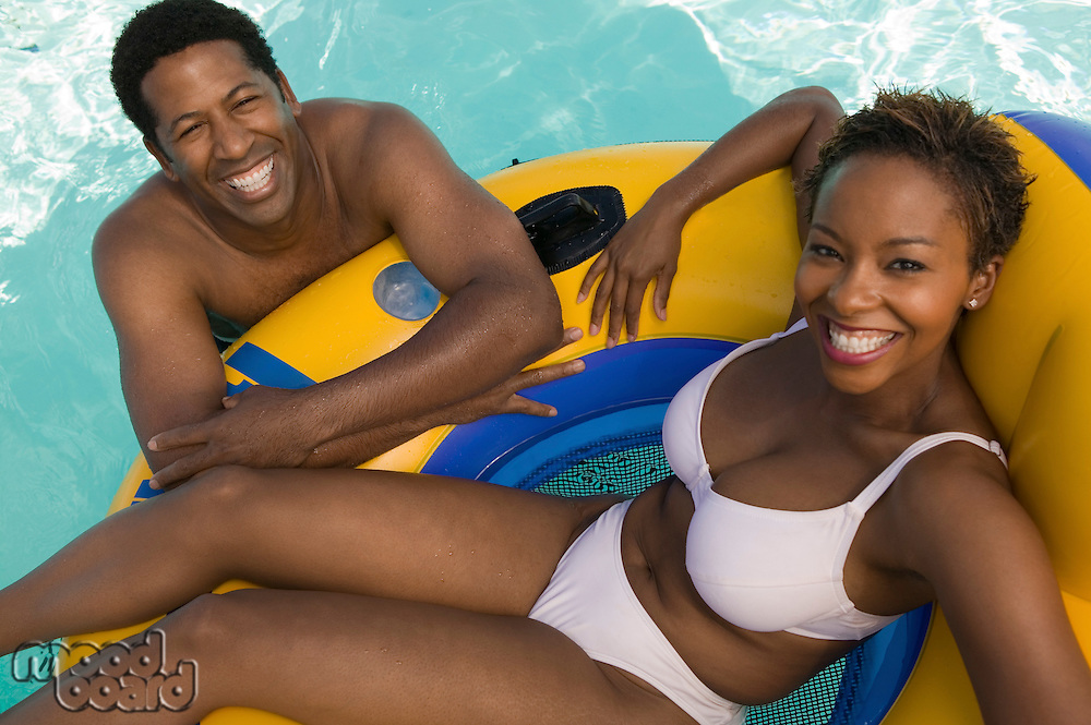 Couple Relaxing in Pool on Inflatable Raft