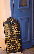 A chalkboard menu outside a taverna on a small back street in Hania, Crete, Greece
