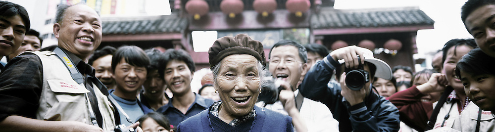 Smiling Woman during photography Festival in Old Stone Street. Duyun, Guizhou Province, China.