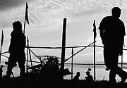 Silhouette of 4 men and fencing against evening sky. Glastonbury 1994