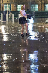© Licensed to London News Pictures . 17/03/2013 . Manchester , UK . A woman wearing very high platform heals walks carefully on the slippery pavement . Evening revellers out in the rain and snow in to the early hours , in Manchester this St Patrick's Day morning (17th March) . Photo credit : Joel Goodman/LNP