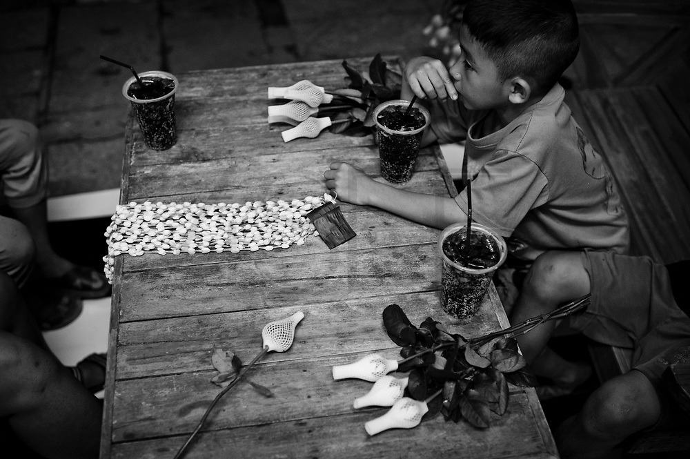 Children getting some rest and something to drink in the area where they sell flowers during the evening and night. They start selling flowers at a very young age, as young as 6 years old.On the banks of a polluted river, in poorly-built houses, live more than a hundred people from the Lahu tribe. They live in a slum in Chiang Mai, Thailand, away from the Lahu people's original way of life. Usually, the Lahu people get their resources from the forest. The slum has been there for decades.