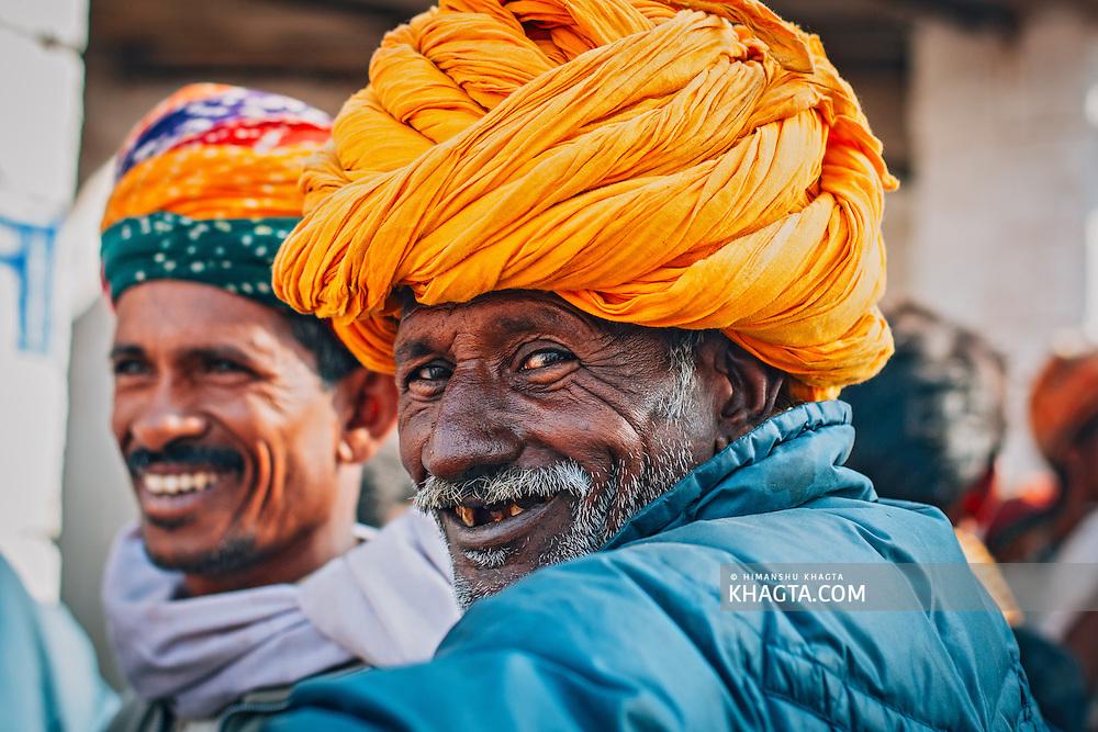 Portrait of an old ethnic Rajasthani man wearing  yellow turban at Ramdeo Cattle Fair, Nagaur