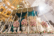 "A float ""paso"" with a statue of the Virgin Mary stands against the lush interiors of the Cathedral of Granada at the conclusion of a procession during the Holy Week. Andalusia, Spain"
