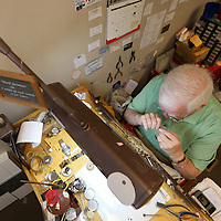 Scott sits at his work talbe that he has had for 40 years as he repairs a customers watch at his shop. Scott also repairs jewelry and does engraving.