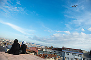 Two young women sit on the old Byzantine land walls in Istanbul, Turkey, looking out over this city of 13 million people. A Turkish Airlines passenger jet flies overhead.