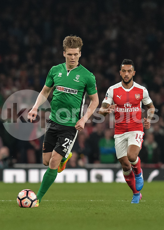 Sean Raggett of Lincoln City in action as Theo Walcott of Arsenal looks on during the The FA Cup sixth round match between Arsenal and Lincoln City at the Emirates Stadium, London, England on 11 March 2017. Photo by Vince Mignott.