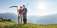 Maria and Christian Thöni on the Alp Stierva on a nice and sunny summer morning in August with sight on the Albula valley and the Lenzer Horn to the right , Parc Ela, Grisons, Switzerland