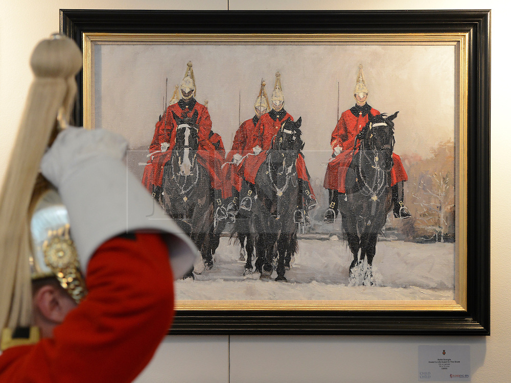 """© Licensed to London News Pictures. 20/04/2012. London, UK . A soldier adjusts his helmet in front of """"Queen's Life Guard in the Snow"""" by Katie Scorgie. A Preview of the Household Cavalrys 'The Best of British' art exhibition. Soldiers walk around the artwork as they prepare to mount duties at Horse Guards Parade. The Queen's Life Guard are inspected before they depart the Barracks for the daily Guard change at 1100. The exhibition runs between 23 - 26 April. Hyde Park Barracks, Ceremonial Gate, South Carriage Drive, London, SW7 1SE. Photo credit : Stephen Simpson/LNP"""