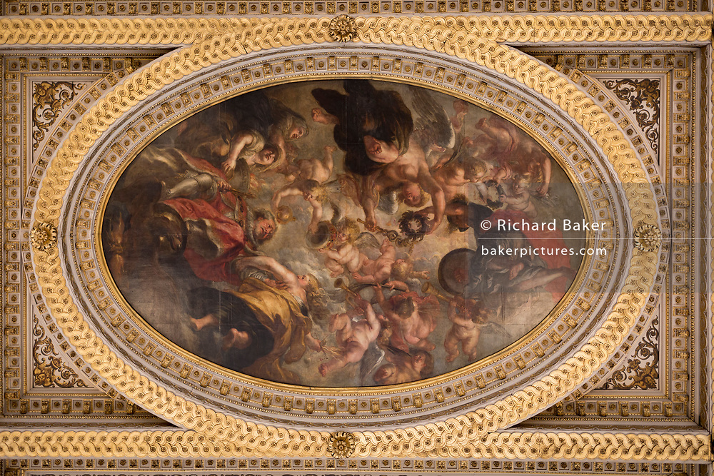 One of the paintings by Paul Rubens on the ceiling of Banqueting House, on 17th September 2017, in Whitehall, Westminster, London, England. The ceiling of the Banqueting House is a masterpiece and the only surviving in-situ ceiling painting by Flemish artist, Sir Peter Paul Rubens. It is also one of the most famous works from the golden age of painting. The canvases were painted by Rubens and installed in the hall in 1636. The three main canvasses depict The Union of the Crowns, The Apotheosis of James I and The Peaceful Reign of James I. Most likely commissioned by King Charles I in 1629-30, this ceiling was one of his last sights before he was executed on a scaffold outside on Whitehall in 1649.