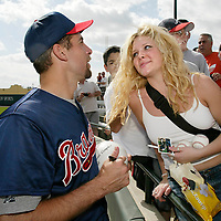 Atlanta Braves pitcher John Smoltz, left, signs autographs during spring training workouts as an adoring fan keeps her eyes on him  Wednesday, Feb. 20, 2002, in Lake Buena Vista, Fla.  (AP Photo/Scott Audette)