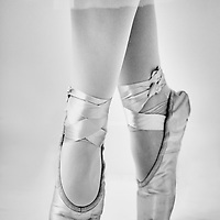 A young girl standing on point in ballet shoes